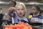 Girl scooping carrots in cafeteria