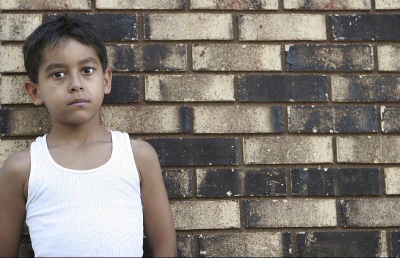 Boy at brick wall