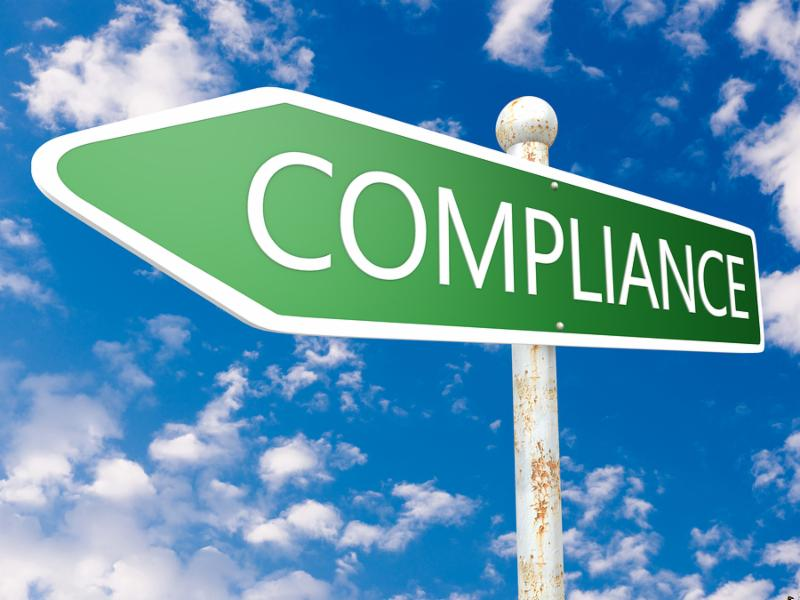 Compliance - street sign illustration in front of blue sky with clouds.