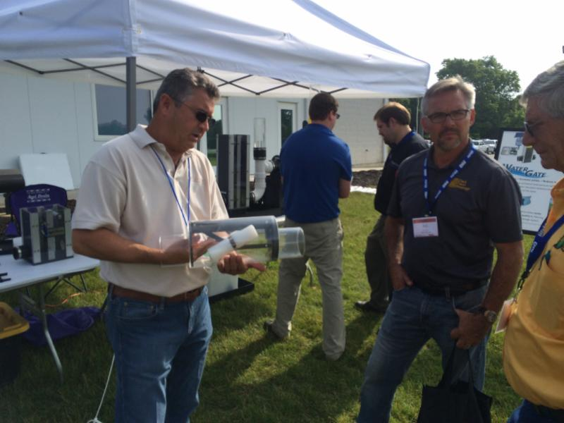 Charlie Schafer (left; President of Agri Drain) with Bob Clark II (center; President of Clark Farm Drainage), discussing subsurface irrigation as a drainage water management practice with an Indiana Farmer at a Successful Farming's: Tools of the Future event at the Purdue University's Beck Ag Center.