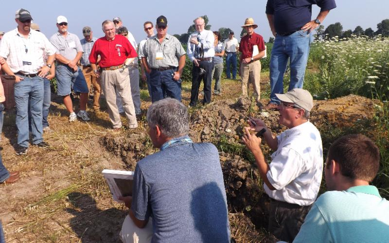 Barry Fisher of NRCS speaks from a soil pit on the Legan Farms tour.