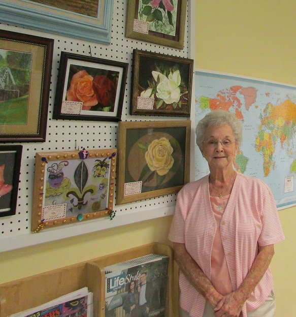 October Artist of the Month Ruby Newcomb in front of her paintings