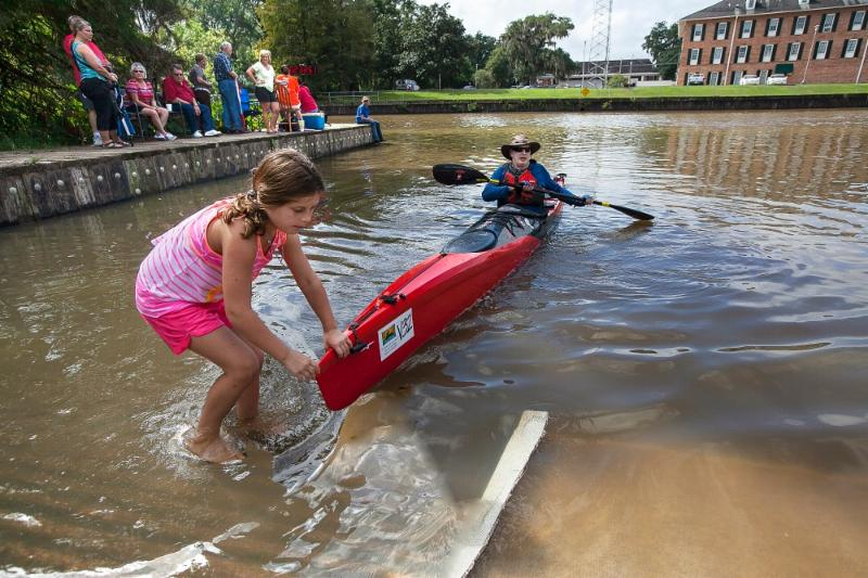 Child pulling canoe at Tour du Teche