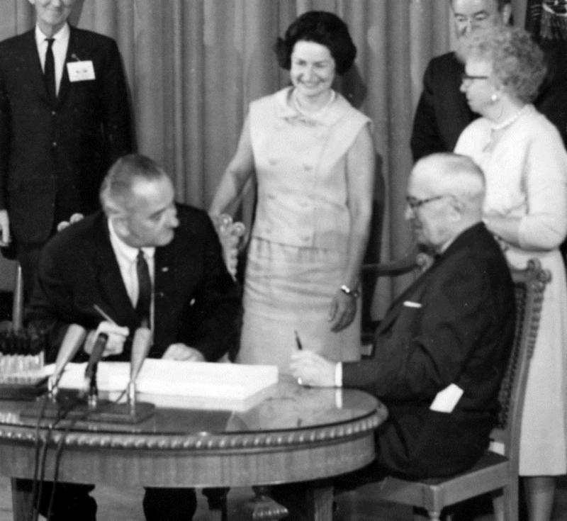 President Lyndon B. Johnson signs Medicare and Medicaid into law with former President Harry S. Truman by his side, July 30, 1965