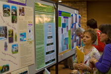 Conference attendee learns from poster presentation.