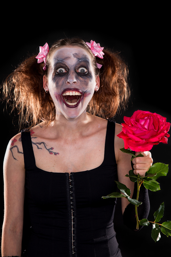 insane funny female clown with red rose in front of black