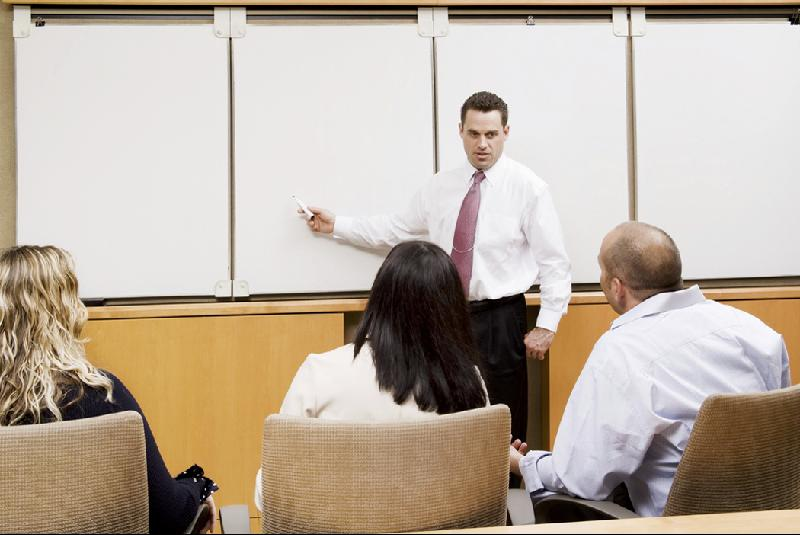 man teaching classroom of adults