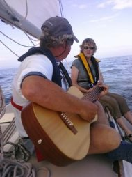 Kathy and I on boat me playing guitar