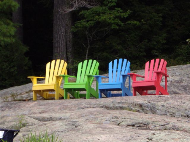 4 Colours of Adirondack chairs on a rock