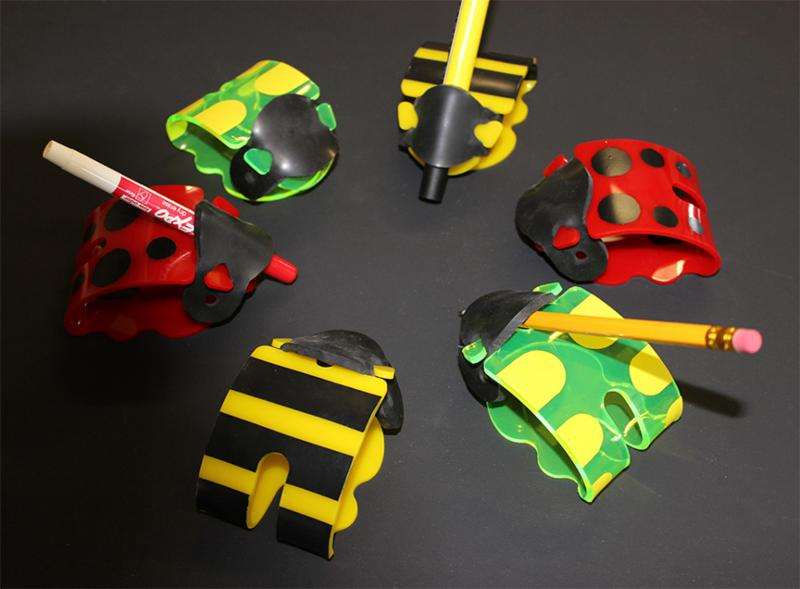 Colorful writing aids in the shape of a ladybug_ holding a pencil or pen