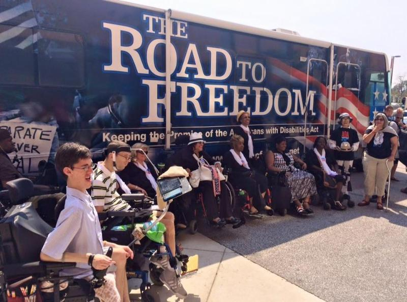 Individuals with wheelchairs in front of ADA Legacy Bus