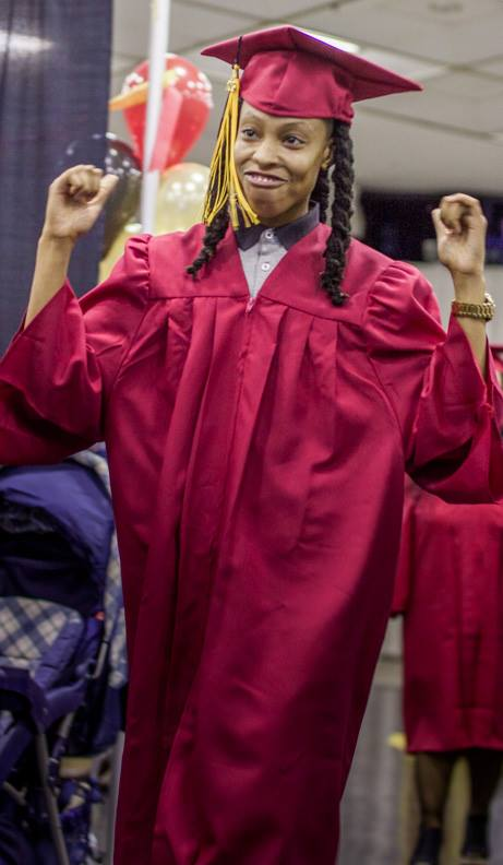 Success student in red cap and gown with hands up in victory