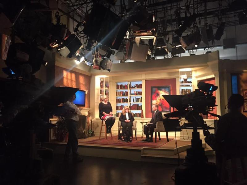 Image of ASL interpreter, MDOD staff person and show host on television set with cameras in foreground