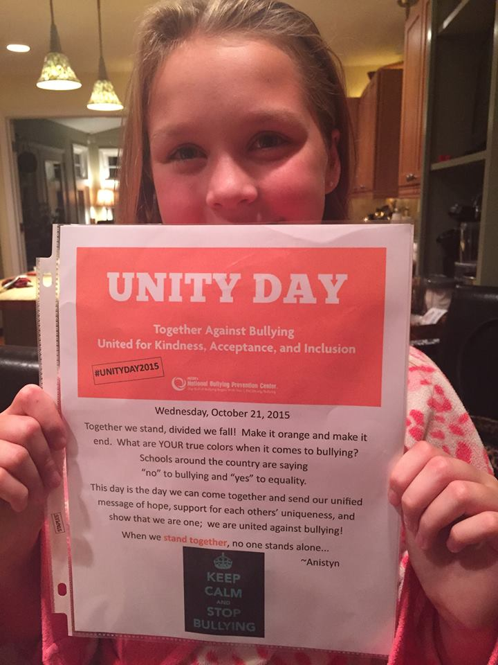 Young girl stands behind Unity Day sign encouraging others to wear orange against bullying.