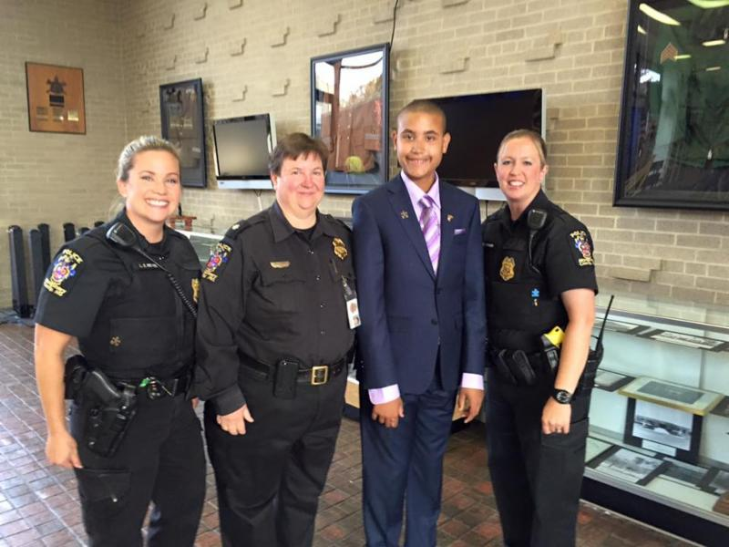 Jake poses in suit with three female Montgomery County police officers in uniform