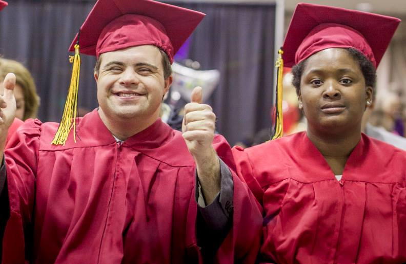 Male success student in red cap and gown giving thumbs up with female student sitting to his left