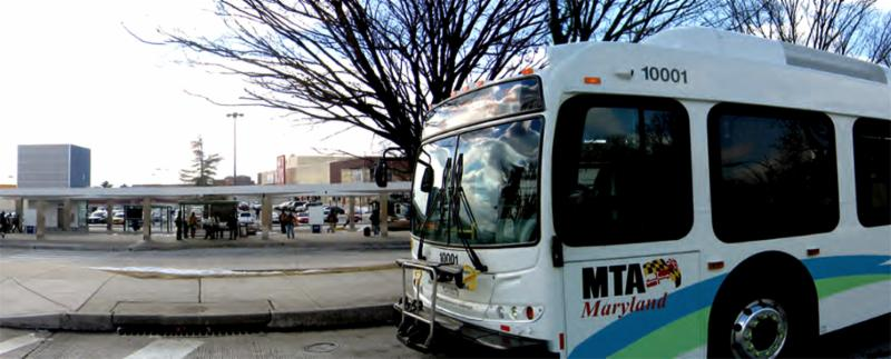 MTA bus pulling up to curb at bus stop in Baltimore