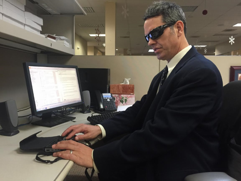 Man who is blind works at desk with computer using assistive technology