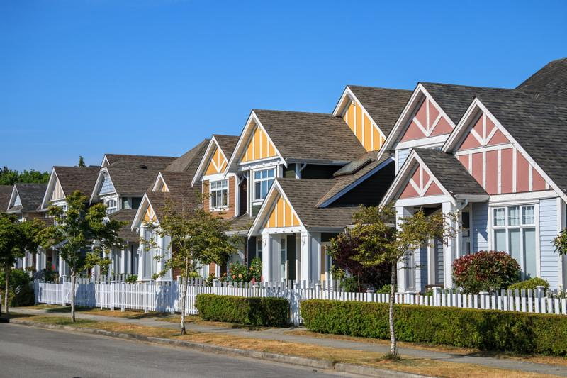 A row of a new houses in Richmond British Columbia Canada. Front yards of the houses and street with trees and bushes.