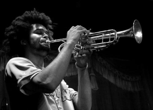 Performer Afro D (Pete Shunghu) playing the trumpet