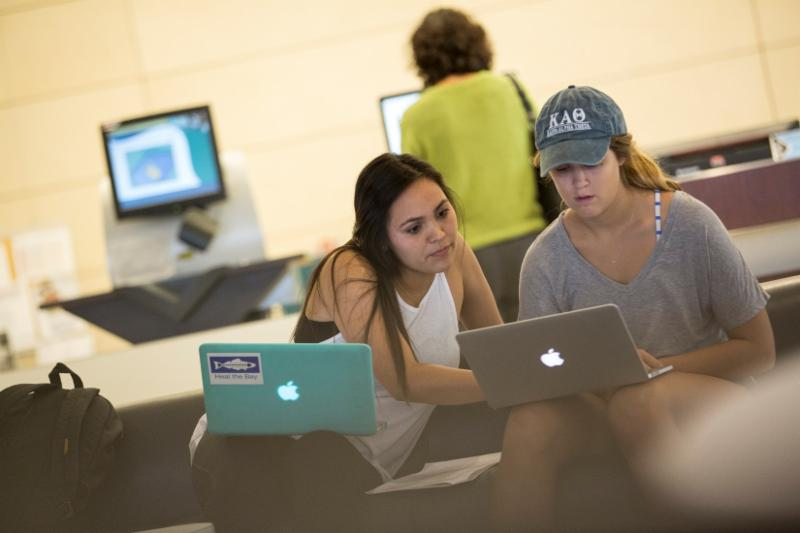 two students using laptops