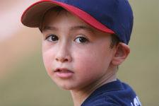 boy in baseball cap looks over shoulder