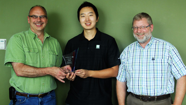 Ryan Kim of Plan LED accepts his award from Michael Lane and Doug Dickson from PSE