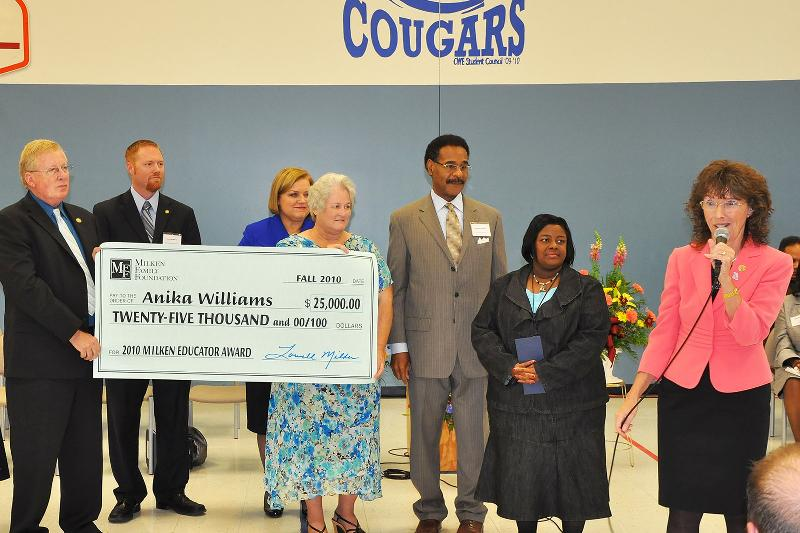 Rep. Holsman watches as a $25,000 check is presented to Anika Williams
