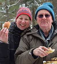 man and woman eating hot dogs