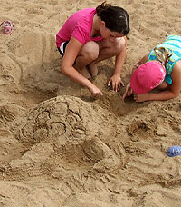 photo of children making sand sculpture