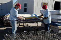 Two men preparing a mattress for recycling