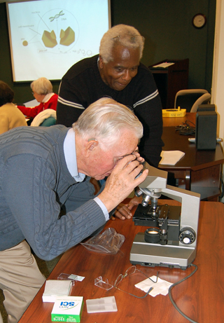2 men at a microscope