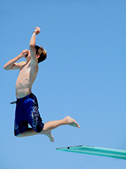 Photo of boy jumping off diving board