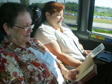 Photo of one woman reading a book, and another woman reading a Kindle.