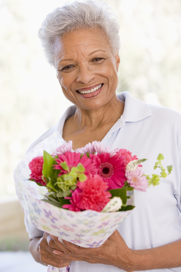 Senior woman holding flowers and smiling