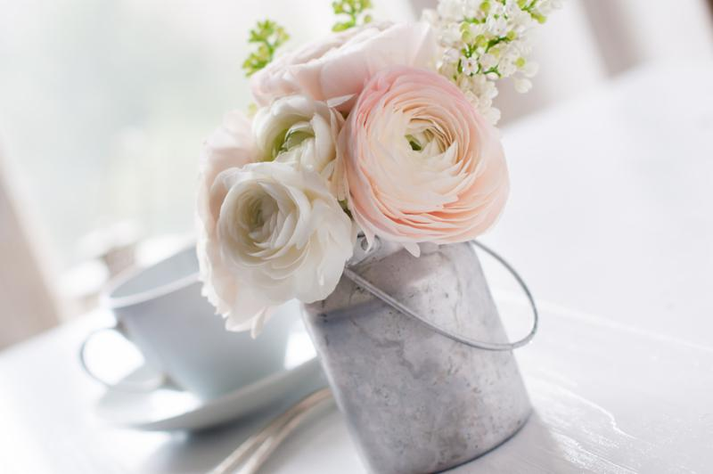 Little delicate elegant bouquet of flowers buttercups and white lilacs in tin can and a teacup on white wooden table morning breakfast