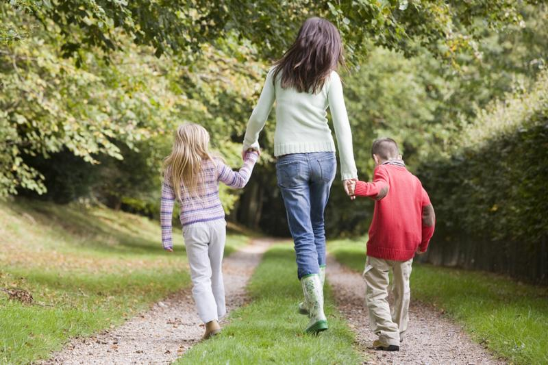Mother and two young children walking on path outdoors  selective focus