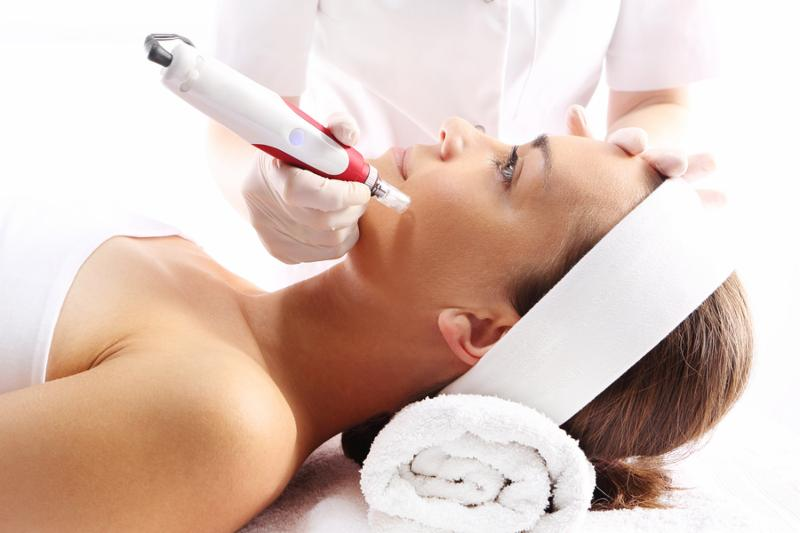 Beautician performs a needle mesotherapy treatment on a woman s face