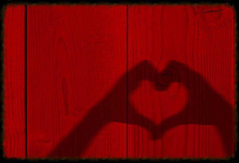 Concept or conceptual Valentine human man and woman hands silhouette as heart or love symbol on old red wood background