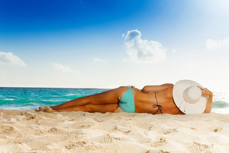 woman with tan laying on white sand beach wearing striped swimwear and big hat     Note  Shallow depth of field