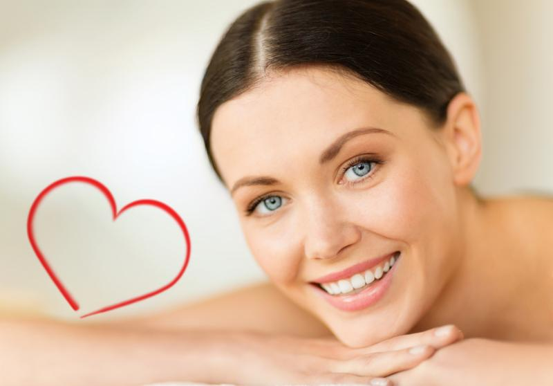 health and beauty, resort and relaxation concept - smiling woman in spa salon lying on the massage desk