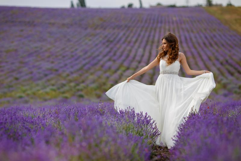 Young bride in wedding dress in the outdoors in a field of blossoming Lavender in the summer.