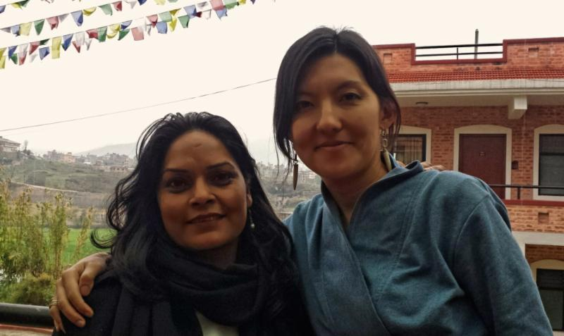 Two women pose for a photo in a village in Nepal