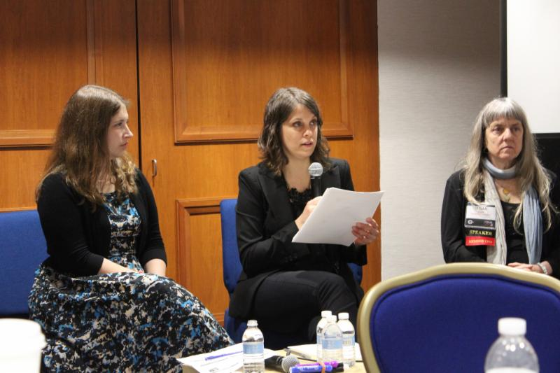 Lisa Adams sitting and speaking alongside two presenters during a conference