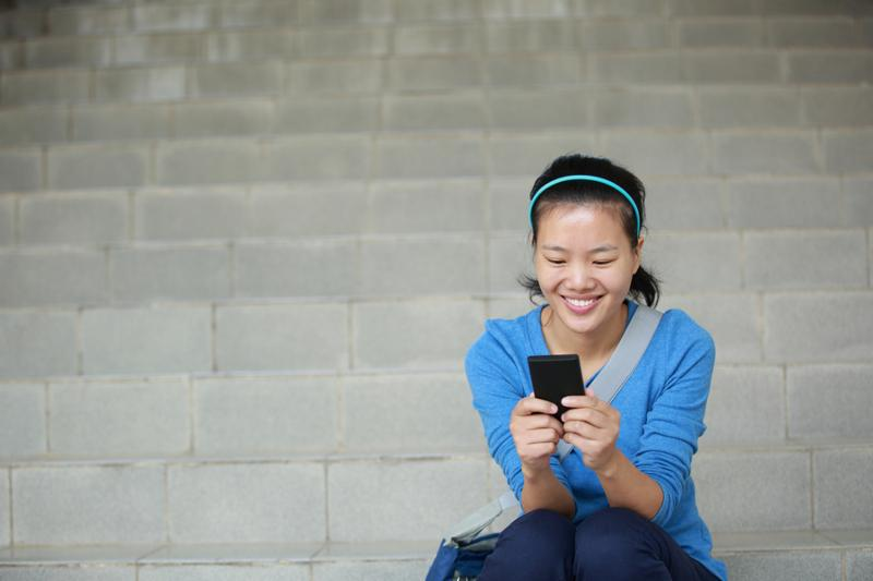 college student use smart phone sit on stairs     Note  Shallow depth of field
