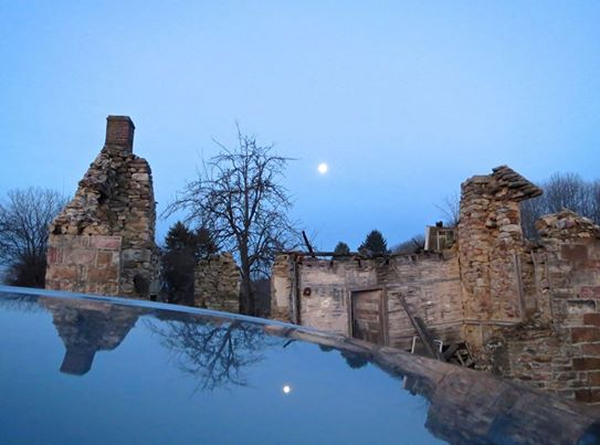 Moon and ruins reflected in roof of car