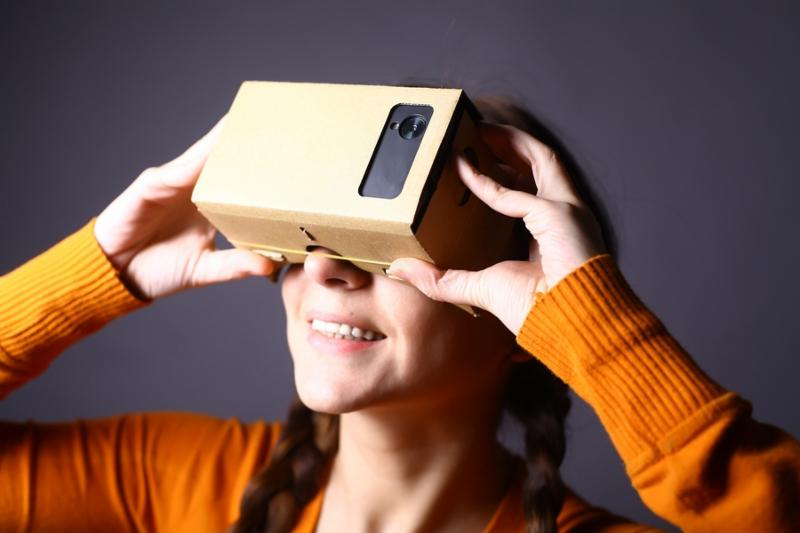 Color shot of a young woman looking through a cardboard a device with which one can experience virtual reality on a mobile phone.