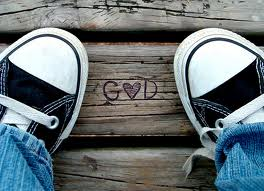 kid in sneakers with God written between feet