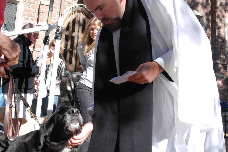 The Rev. Jed Fox blesses a parishioners dog.