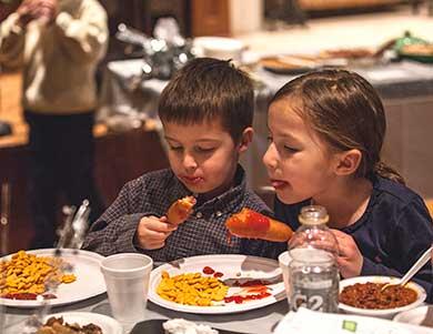 Kids enjoying the annual meeting corndogs.